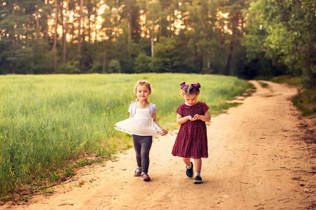 夏の森の小道を歩く二人の少女