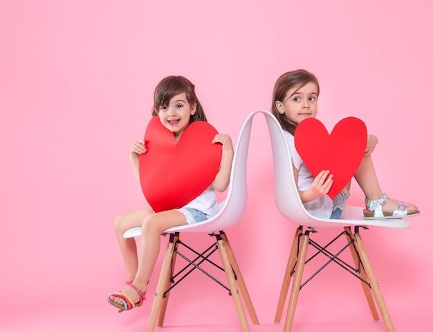 色付きの壁にハートを持つ2人の少女