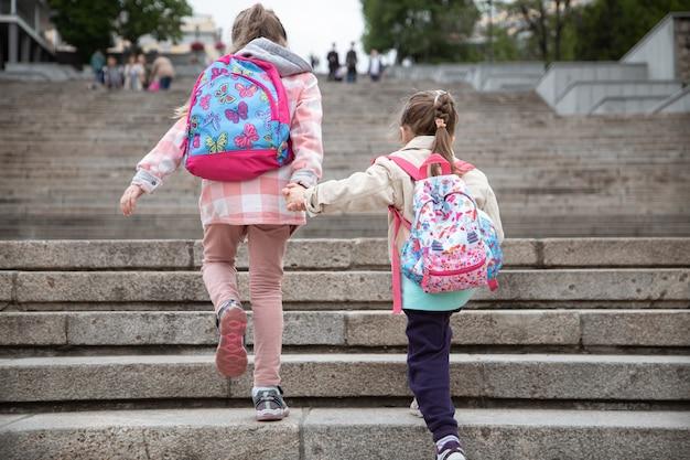 バックパックを背負った二人の少女が手をつないで、後ろから眺めながら階段で学校に通う。