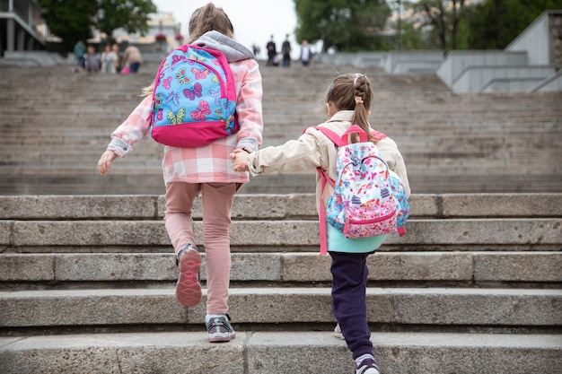 Two little girls with backpacks hold hands and go to school on the steps, view from the back.