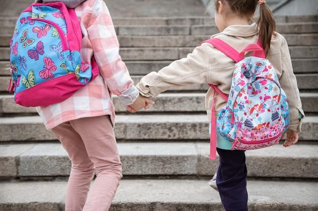 아름다운 배낭을 등에 메고 두 어린 소녀가 함께 학교에갑니다. 어린 시절 우정 개념.
