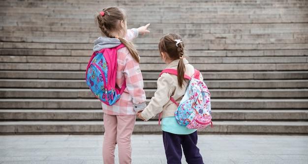 美しいバックパックを背負った二人の少女が手をつないで一緒に学校に通っています。子供の頃の友情の概念。