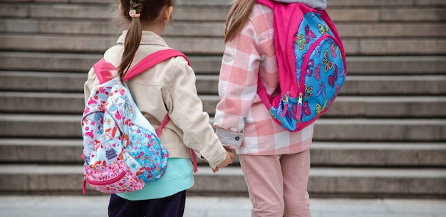 Two little girls with beautiful backpacks on their backs go to school together hand in hand close up.