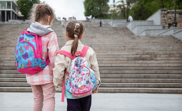 Two little girls with beautiful backpacks on their backs go to school together hand in hand.