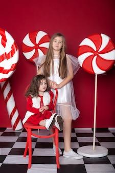 孤立した赤い背景に大きなクリスマスキャンディーを持つ2人の少女