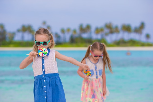 Two little girls with bright tasty lollipops on white beach