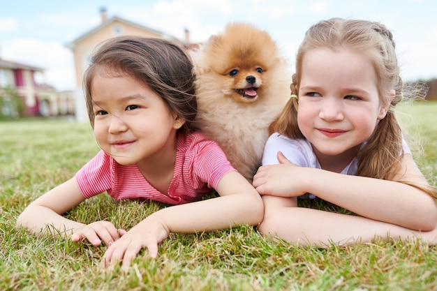 Two little girls with cute puppy outdoors