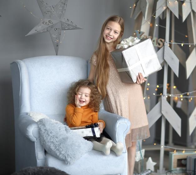 양식에 일치시키는 크리스마스 트리 근처에 서 선물을 가진 두 어린 소녀.