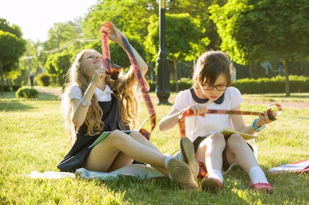 Две маленькие девочки с интересом и удивлением смотрят на фото негативы