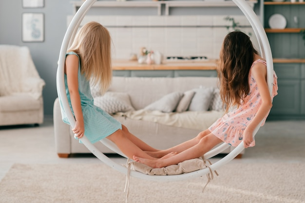 Two little girls with long hair covering their faces sitting at swing in room