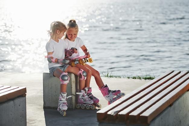 호수 근처 야외에서 롤러 스케이트와 두 어린 소녀