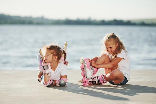 湖の近くの屋外でローラースケートをしている2人の少女