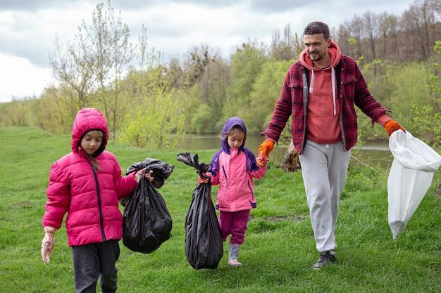Две маленькие девочки с папой в мешках для мусора в поездке на природу убирают окружающую среду.