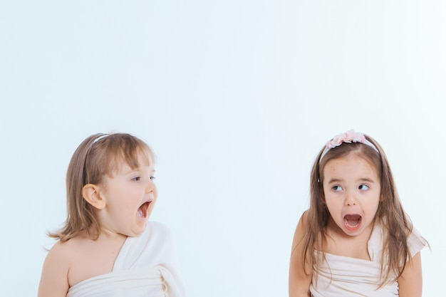 Two little girls with their mouths wide open on a white background. the children are playing. the concept of education , childhood, emotions, dentistry, surprise, friendship. copy space