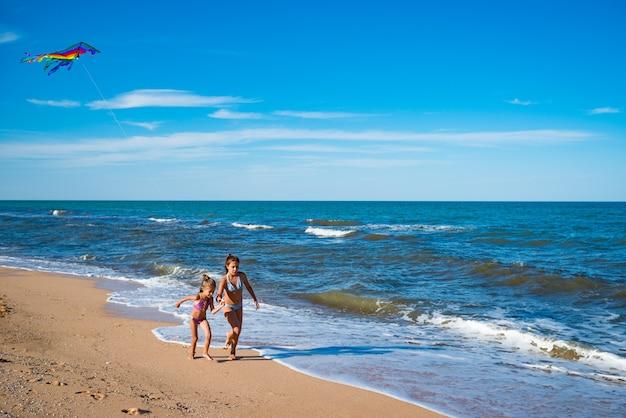 海沿いの砂浜を凧で走る2人の幸せな陽気な女の子。晴れた暖かい夏の日。アクティブな子供のゲームの概念。コピースペース