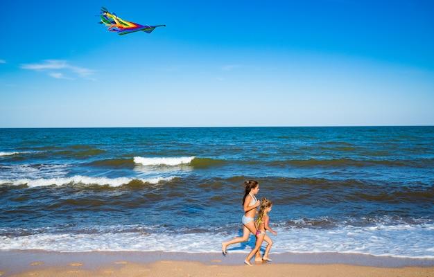 Две маленькие счастливые жизнерадостные девочки бегают с воздушным змеем по песчаному берегу у моря. солнечный теплый летний день. понятие об активных детских играх. copyspace