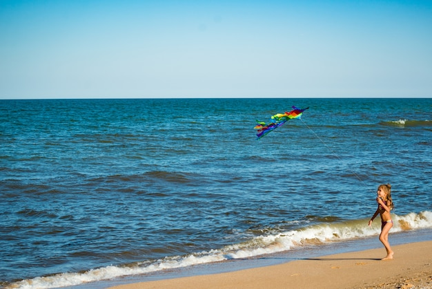 Две маленькие счастливые жизнерадостные девочки бегают с воздушным змеем по песчаному берегу у моря