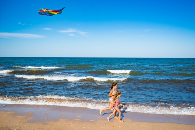 Two little happy cheerful girls run with a kite on the sandy shore by the sea. sunny warm summer day. concept of active children's games. copyspace
