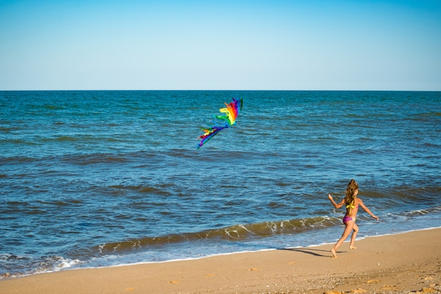 Two little happy cheerful girls run with a kite on the sandy shore by the sea