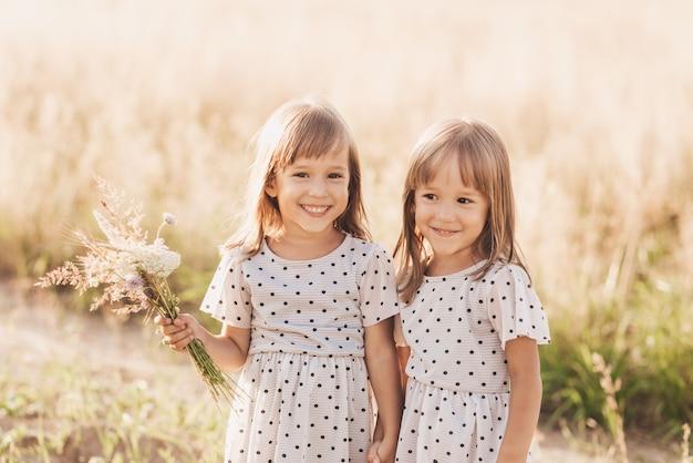 여름에 자연에서 함께 노는 두 명의 작은 행복한 일란성 쌍둥이 소녀. 여자 우정과 청소년 개념입니다. 활동적인 아이들의 라이프스타일.