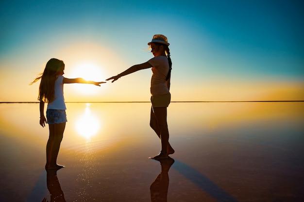 Две маленькие счастливые сестры гуляют по зеркальному розовому озеру, наслаждаясь теплым вечерним солнцем