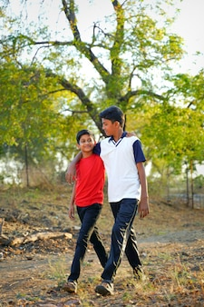 Two little indian brother walking on road