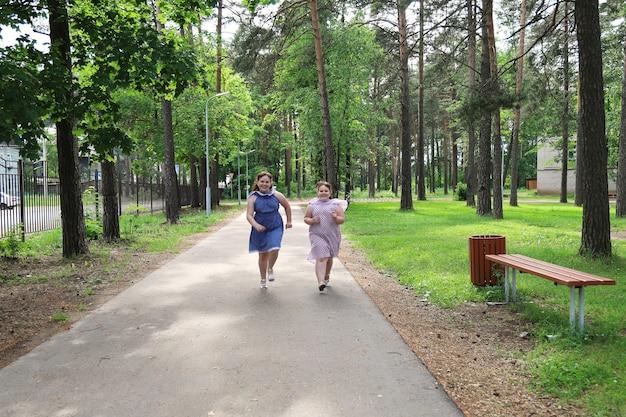 Две маленькие радостные девочки бегают по дорожке в заброшенном парке