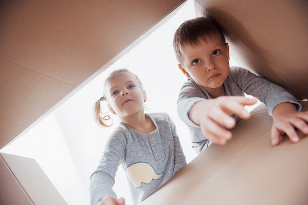 Two a little kids boy and girl opening cardboard box and looking inside with surprise
