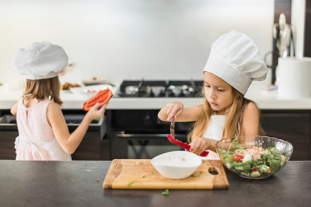 Two little kids in chef hat preparing food in kitchen