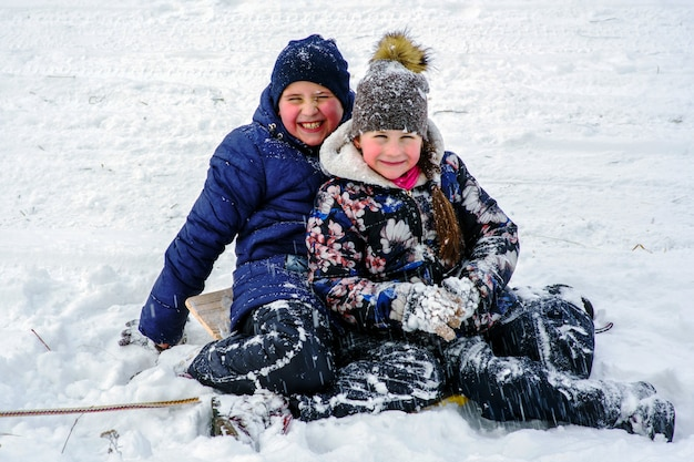 Two little kids in colorful clothes playing outdoors during snowfall. active leisure with children in winter on cold days.