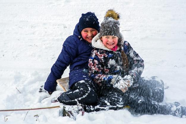 눈이 내리는 동안 야외에서 노는 화려한 옷을 입은 두 명의 어린 아이. 추운 날 겨울에 아이들과 활동적인 여가.