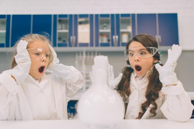 학교 실험실에서 화학을 학습하는 실험실 외 투에있는 두 명의 작은 아이. 실험실 또는 화학 캐비닛에서 실험을하는 보호 안경에 젊은 과학자. 위험한 실험.