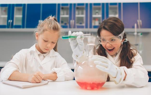학교 실험실에서 화학을 배우는 실험실 코트에 두 명의 작은 아이. 실험실 또는 화학 캐비닛에서 실험을 만드는 보호 안경의 젊은 과학자. 실험을위한 재료 연구.