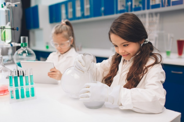 Two little kids in lab coat learning chemistry in school laboratory. young scientists in protective glasses making experiment in lab or chemical cabinet. working on a tablet.