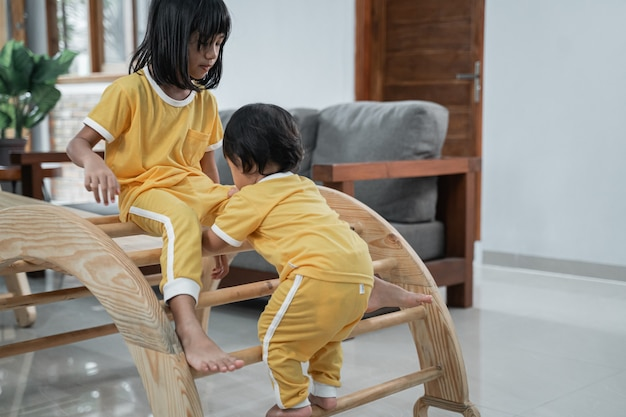 Two little kids playing in pikler triangle toys in the living room background