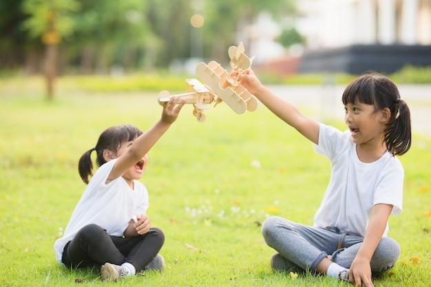 낮 시간에 공원에서 판지 장난감 비행기를 가지고 노는 두 어린 아이
