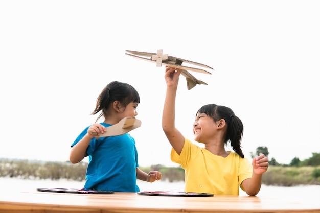 낮 시간에 공원에서 판지 장난감 비행기를 가지고 노는 두 어린 아이.