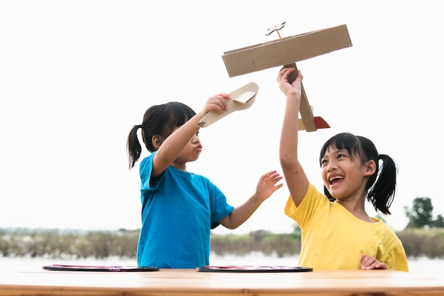 Two little kids playing with cardboard toy airplane in the park at the day time