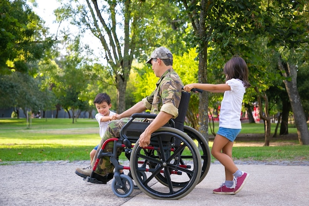 都市公園の車椅子で軍の障害者のお父さんと一緒に歩いている2人の小さな子供。側面図。戦争または障害の概念のベテラン