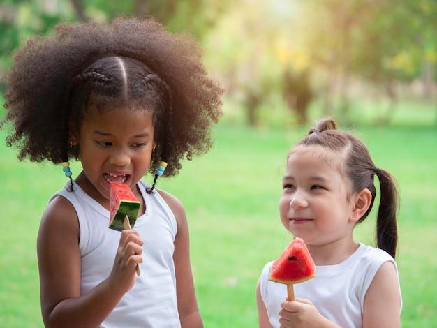 Two little lovely girls of various ethnic having fun eating watermelon in park