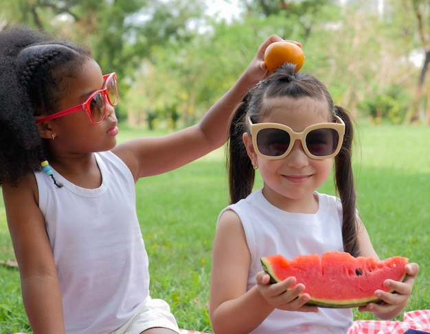 Two little lovely girls of various ethnic having fun eating watermelon in park.