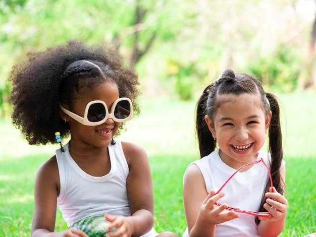 Two little lovely girls of various ethnic having fun in park on summer day.