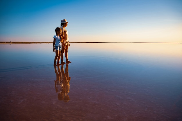 Two little lovely happy sisters are walking along the mirror-like pink salt lake enjoying the warm summer sun in the long-awaited vacation