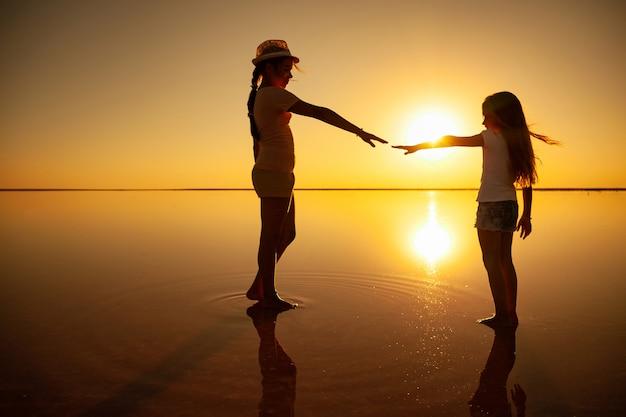Две маленькие милые счастливые сестры гуляют по зеркальному розовому соленому озеру, наслаждаясь теплым летним солнцем в долгожданном отпуске.