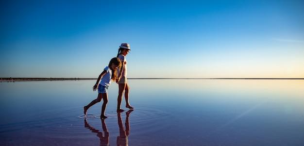 오래 기다렸던 휴가에 따뜻한 여름 햇살을 즐기며 거울 같은 핑크빛 소금 호수를 따라 걷고있는 두 명의 사랑스럽고 행복한 자매