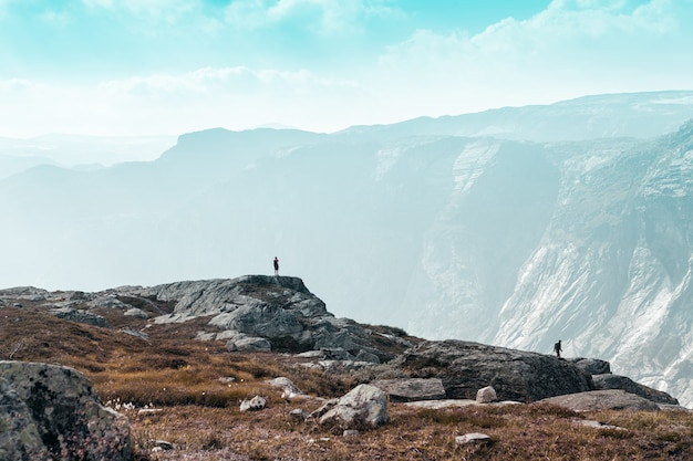 장엄한 노르웨이 산에 대항하는 두 명의 작은 사람