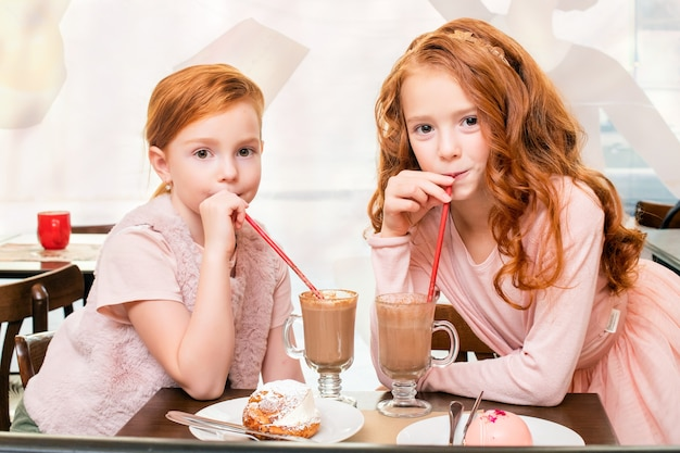 Two little red-haired girls at a table in a cafe, drinking milkshakes