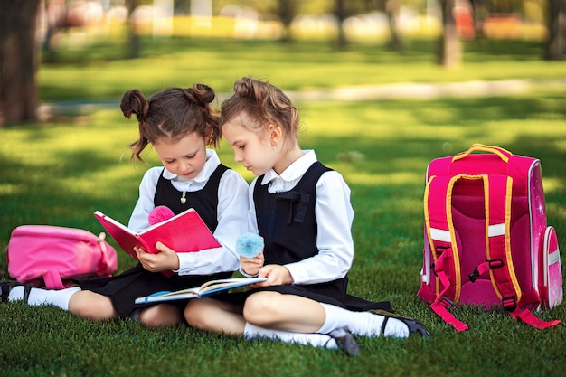 Two little school girls with pink backpack sitting on grass after lessons and read book