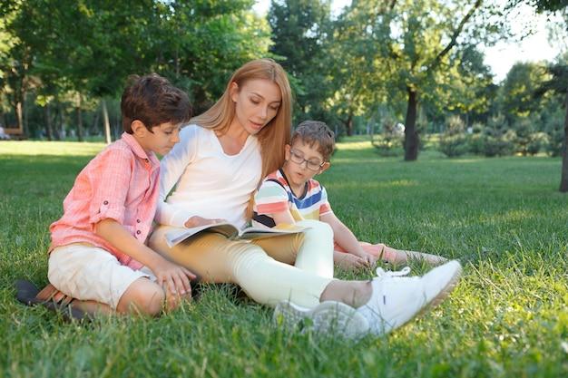 Два маленьких школьника читают книгу со своей учительницей на открытом воздухе в парке