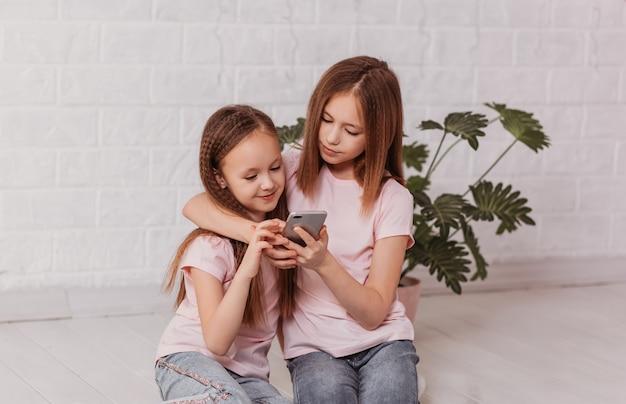 2人の小さな女子高生がスマートフォンの画面を見る
